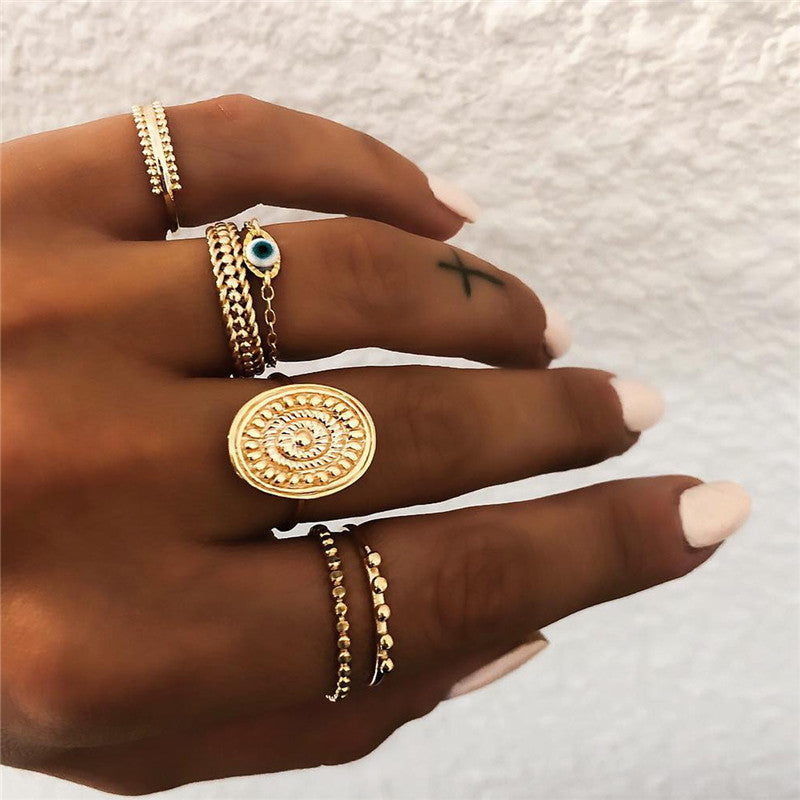 6 vintage gold rings on woman's hand