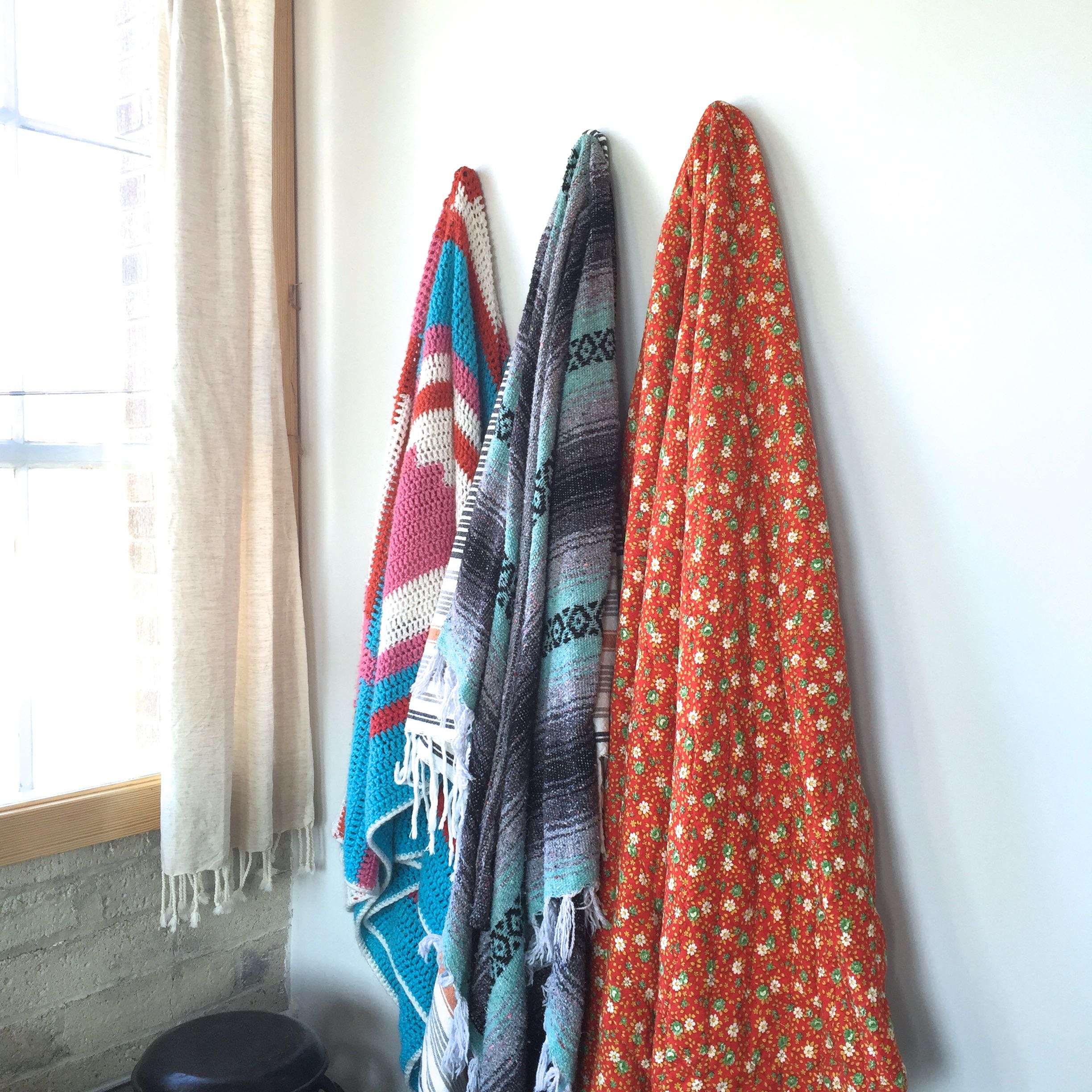 Clavo nails help in organizing a collection of vintage boho throws.