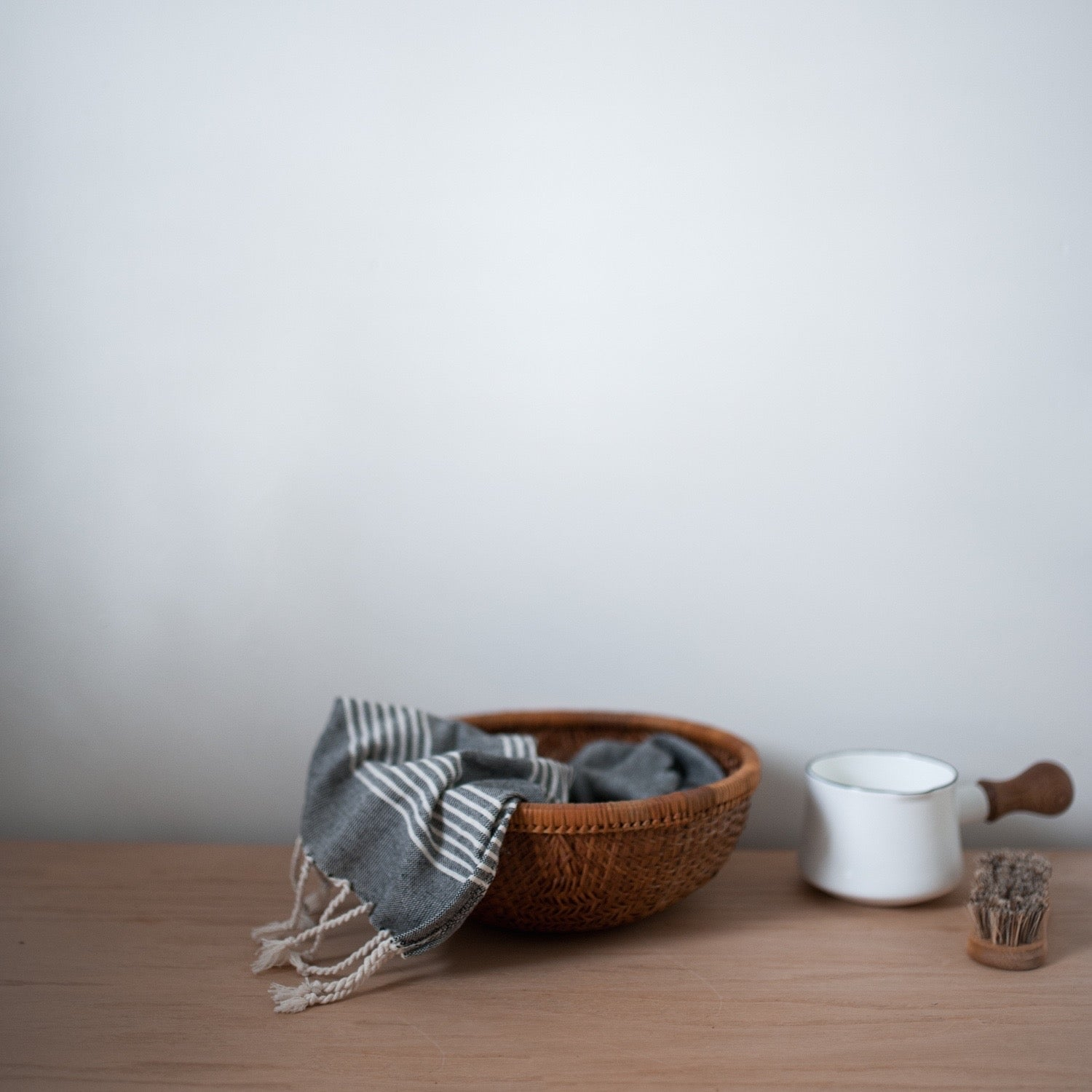 Charcoal grey turkish hand towel in a woven basket.