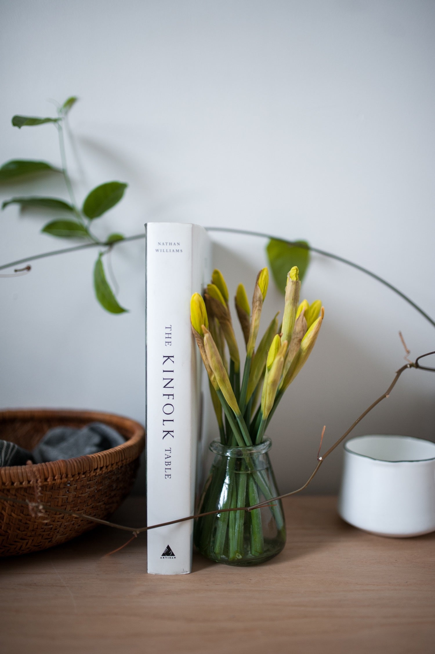 Kinfolk styled tabletop with fresh cut spring flowers in a hand blown glass vase.