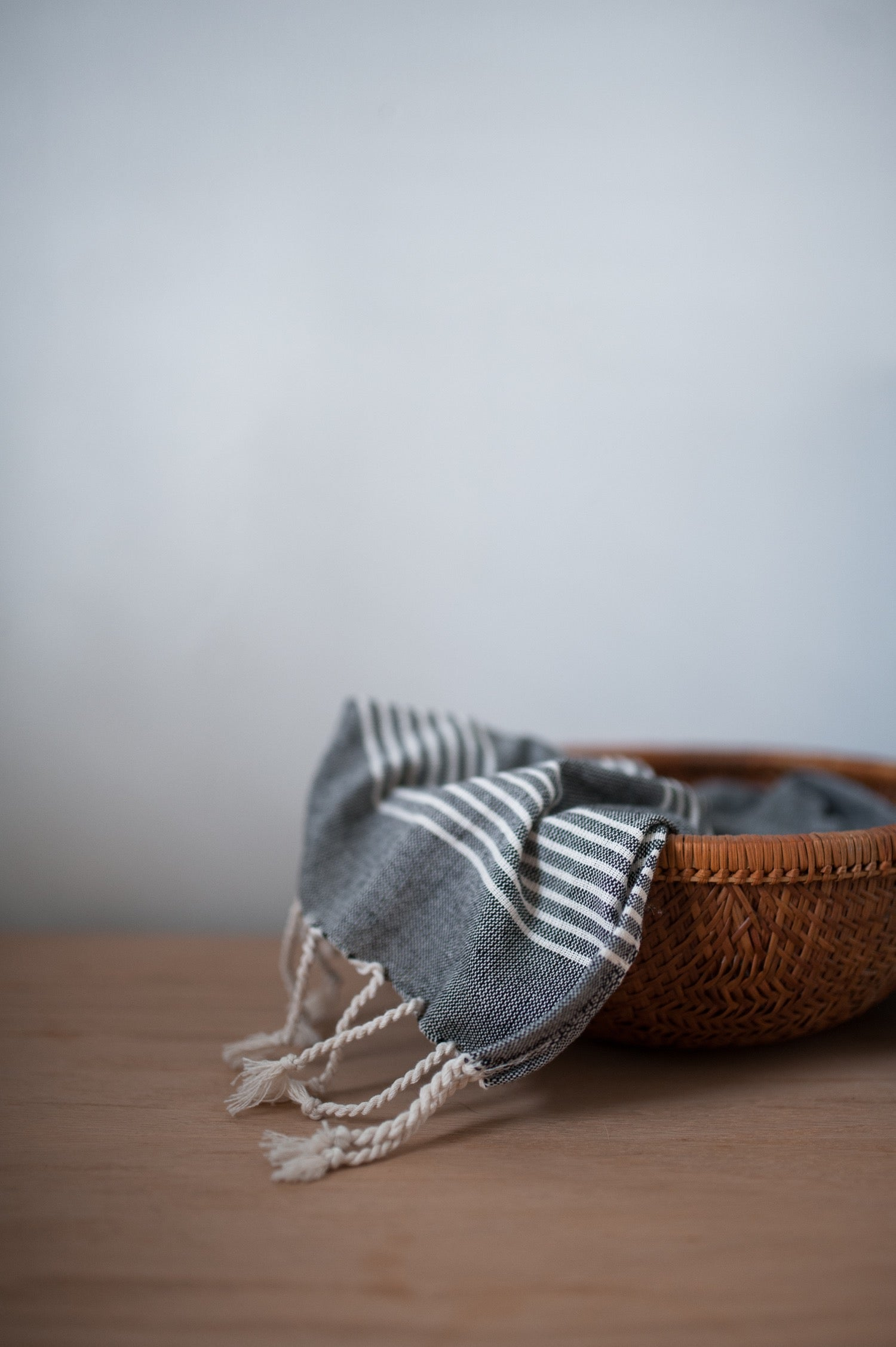 Turkish hand towel in charcoal and a woven basket.