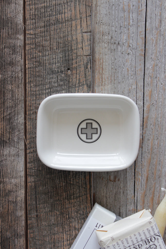 Ceramic apothecary soap dish with vintage red cross symbol.