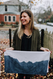 Morgan displays her natural indigo dip dyed tea towel made in Asheville.