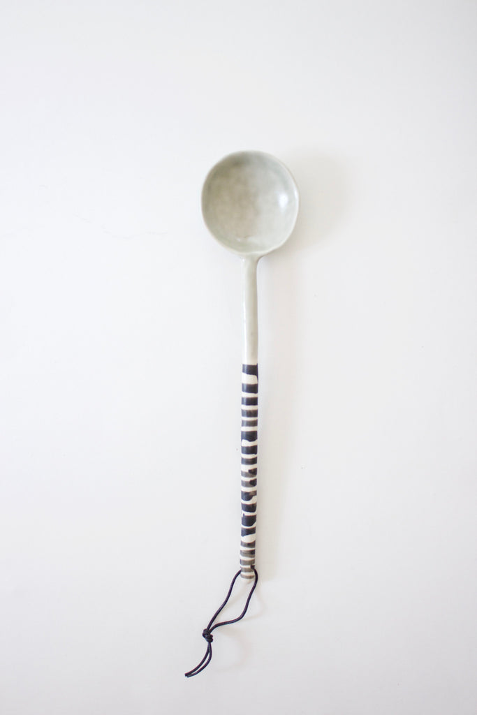 Ceramic serving spoon in a muted sage made by hand.