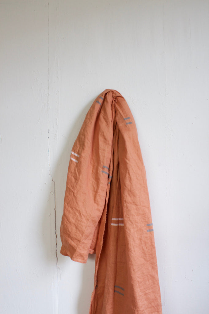 Salmon linen throw with grey and white dash pattern made in the USA.