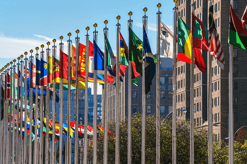 A semi circle of national flags in front of the UN building.
