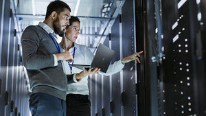 Two IT professionals examining servers