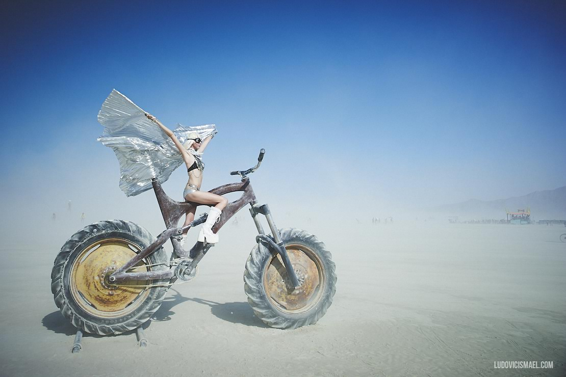 Girl on huge art bike in the dust