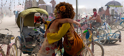 Burners hugging with bicycles in the background
