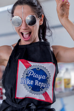Person wearing a Playa Bike Repair apron having fun