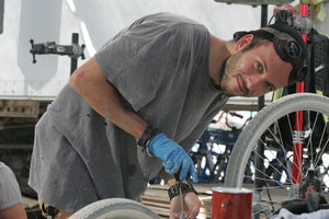 Member of Playa Bike Repair working on a bicycle