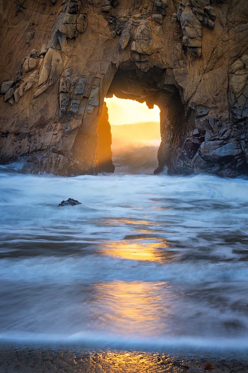 Sunset glow through an arch in big sur california.