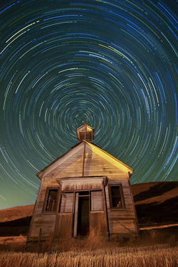 An old schoolhouse with the night sky above it