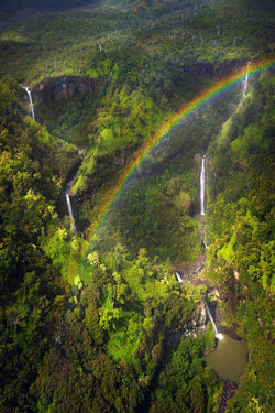 A rainbow appears above waterfalls in Kauai Hawaii