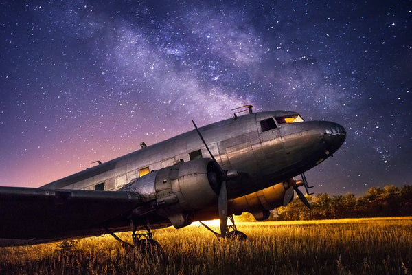 An abandoned DC-3 plane sits under the stars