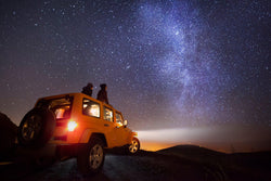 a Jeep sits under the stars