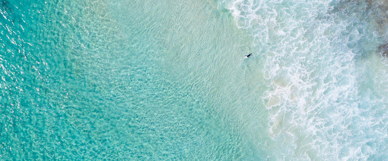 An aerial of a surfer paddling out through the clear waters of Western Australia.
