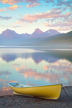 A yellow canoe sits on the shores of Lake McDonald in Glacier National Park