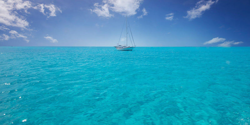 Crystal clear water and a sailboat in The Exumas, Bahamas. By Lijah Hanley.