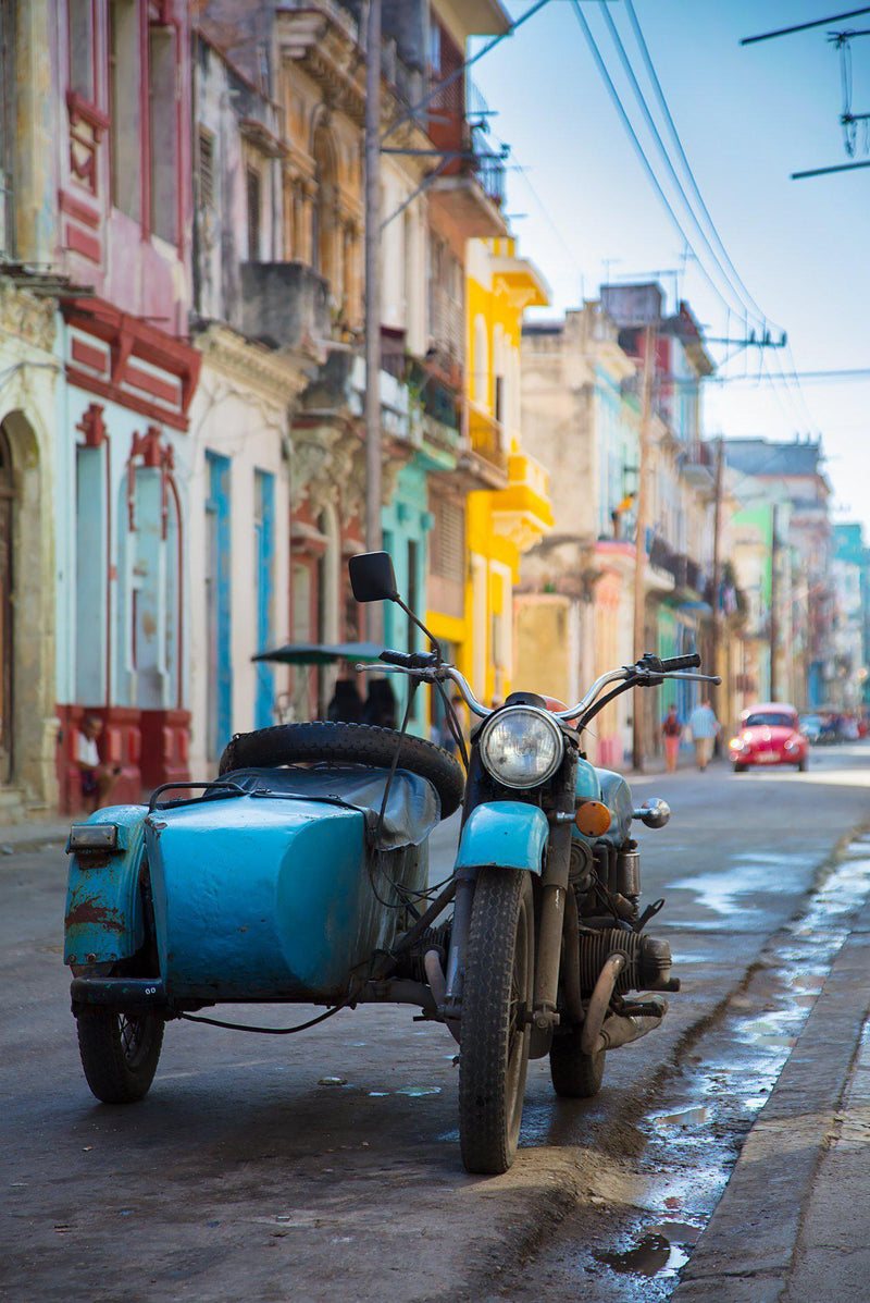 A motorcycle and sidecar sit in the streets in Havana Cuba
