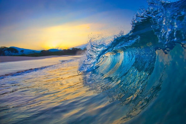 A crashing wave at sunrise on Maui
