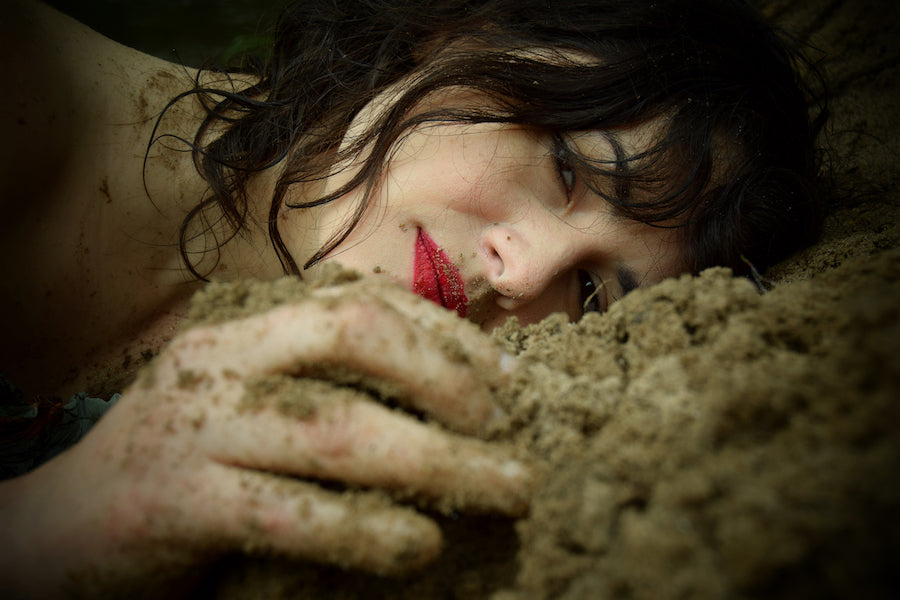 Pop Surrealist Artist Lisa Diakova Woman with Red Lips Lying in Sand and Dirt