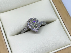 A pear shape diamond halo ring with diamond shoulders in pt950