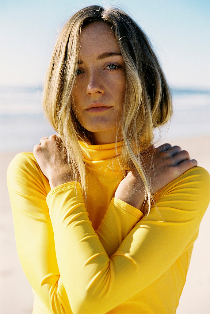 Shay Maclean shot on film by Ming Nomchong for Sea Bones Byron Bay | www.saltgypsy.com Shay wears Salt Gypsy Turtleneck in Gold and reversible Drifter bottoms in Navy Star/Gold | #saltgypsy #mingnomchong #seabonesbyronbay #styleinthelineup #sustainablesurf #surffashion