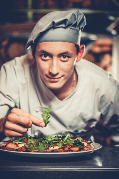 Chef looking towards the camera while topping a pizza with herbs.