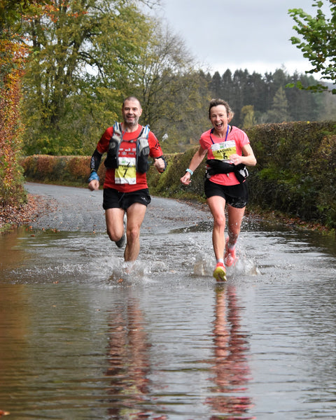 Two smiling runners splash through a puddle during the Brathay 10in10 challenge 2020