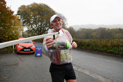 A runner collects nutrition supplies from feed station during the Brathay 10in10
