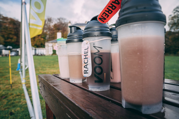 Protein shakers with VOOM Rapid Recovery set out on a table at the event finish area