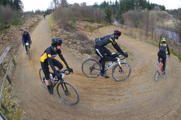 Several gravel riders take on a corner on a dry trail