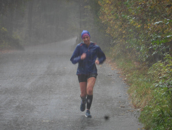 Dianne Morris running through thrashing rain as she makes her way around the Brathay 10in10