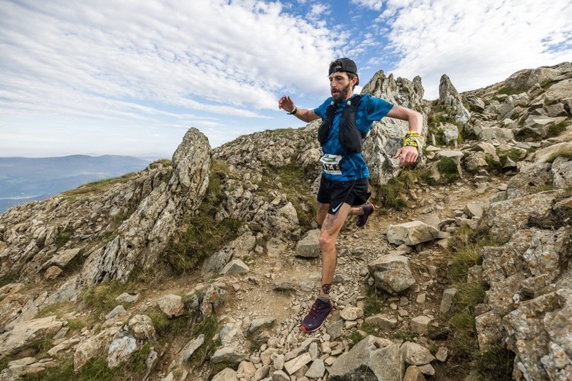 A male mountain runner heading downhill over some rough terrain in Wales during the Dragons Back race