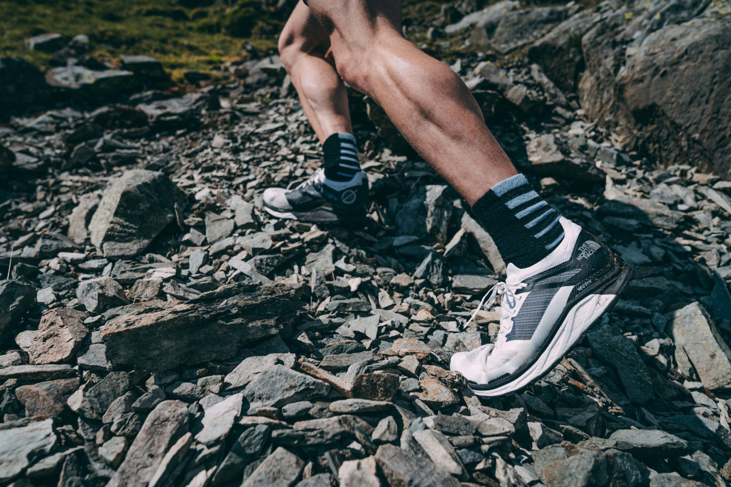 A close up of white trainers and legs of an uphill runner on loose slate terrain