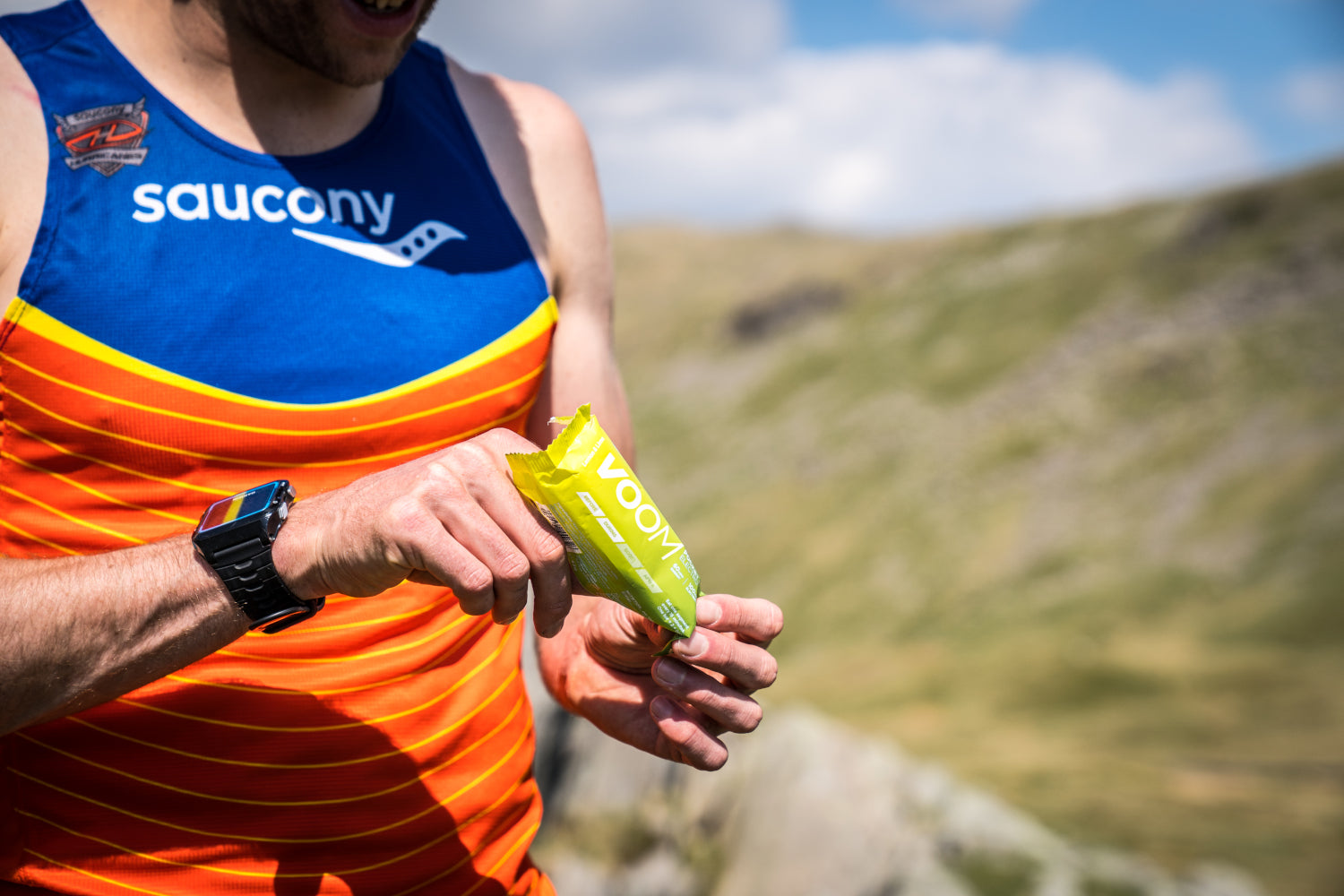 A runner opening an electrolyte Pocket Rocket energy bar with mountains in the background