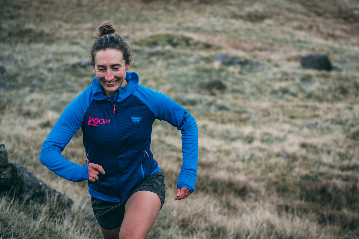 A female runner with a big smile on her face strides out up a grassy hill