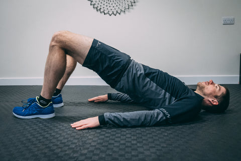 A runner doing a strength and conditioning session in the gym holds a glute bridge