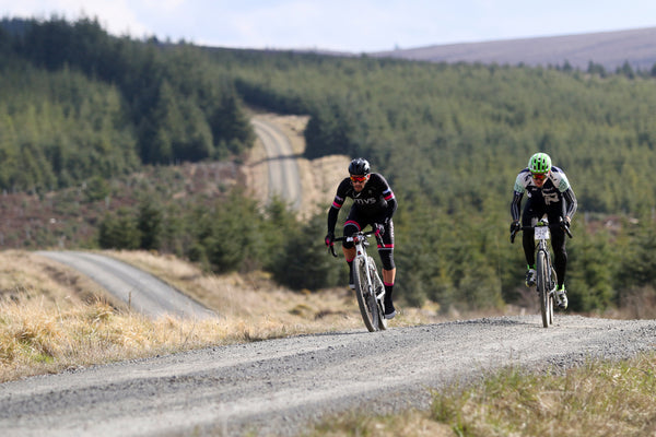 Two cyclists sprint up a hill during a gravel ride with a large expanse of forest behind them