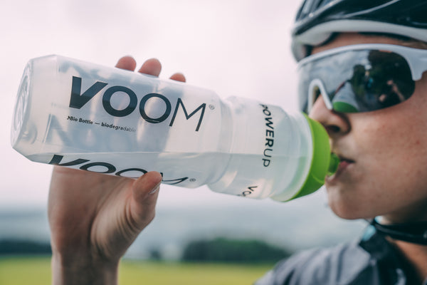 A female cyclist drinks VOOM Electrolyte drink from a bottle to improve hydration