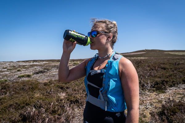 A female runner uses a sports hydration drink to improve hydration on a hot day