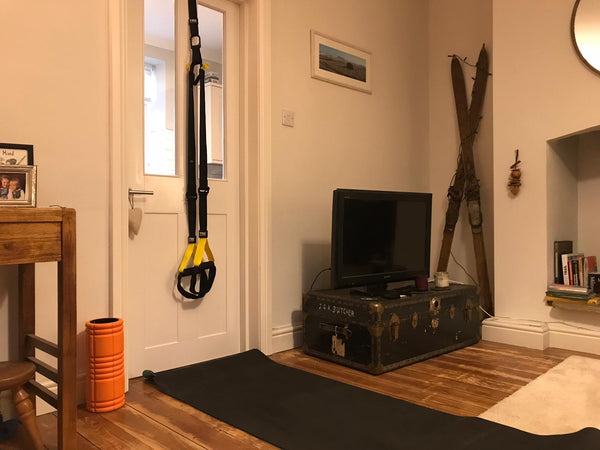 A TRX suspension trainer and foam roller set out with a fitness mat for home training in someone's living room
