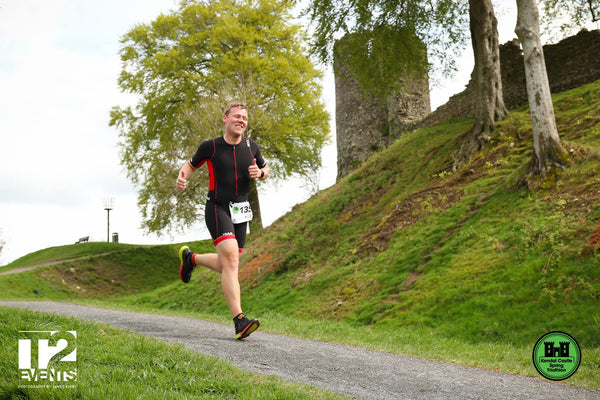 A runner heads down the hill in front of Kendal Castle during the triathlon event