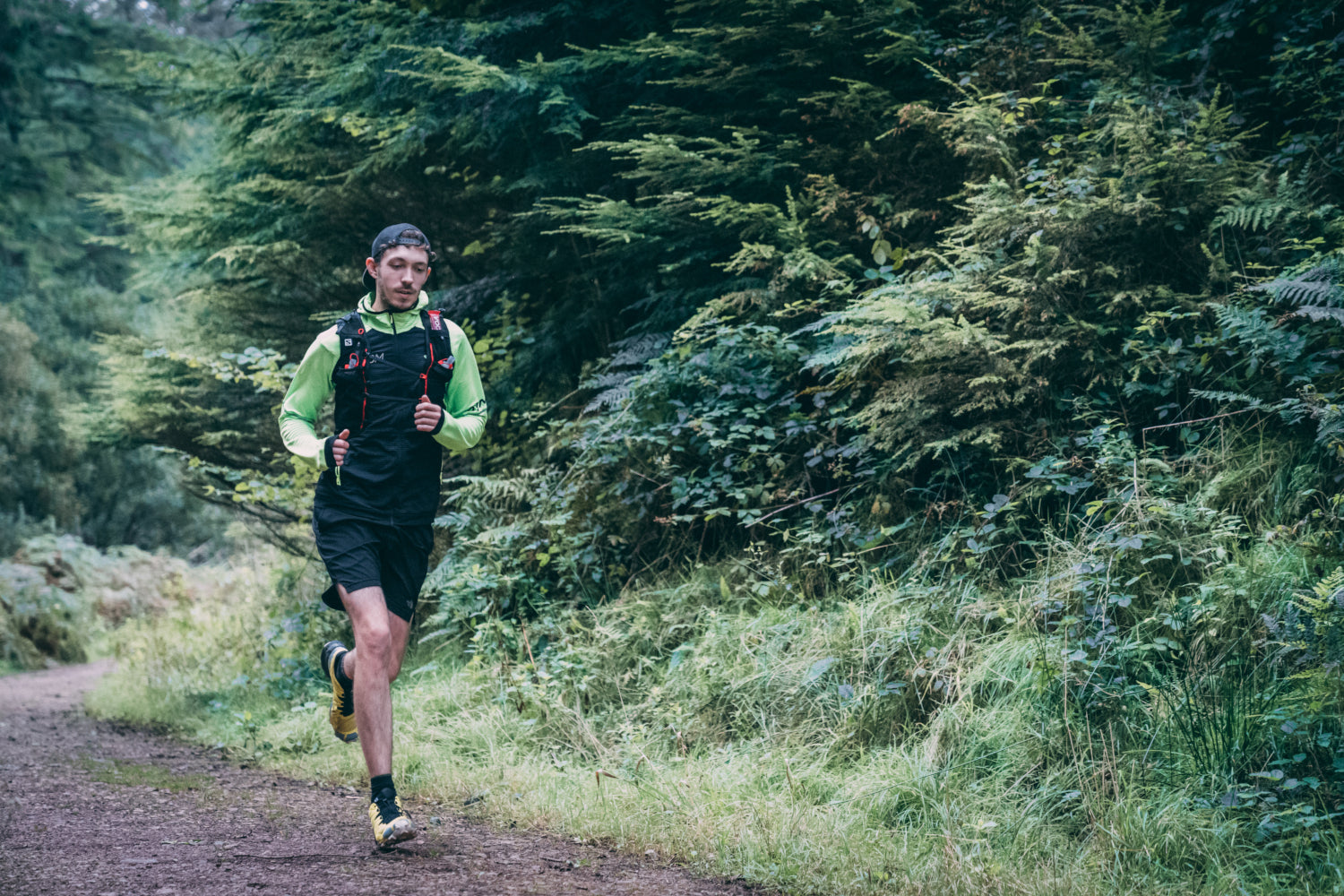 A trail runner heads along an off road path through the woods