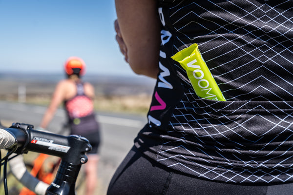 A VOOM Pocket Rocket Electro Energy bar protruding from the rear pocket or a cycling jersey