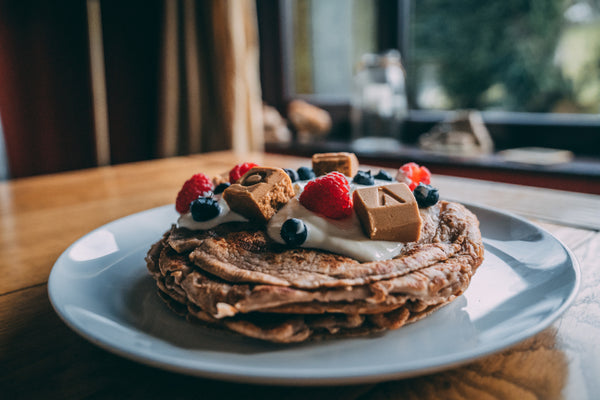 A stack of protein pancakes topped with VOOM RecoverFudge and berries