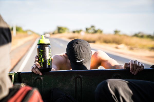 A male runner leaning on the back of a jeep with a bottle of sports hydration electrolyte drink in hand