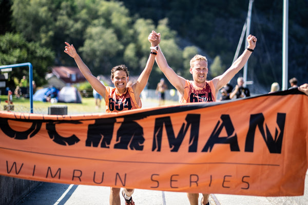 A mixed pair of competitors reach the finish banner of the Rockman swimrun event in Norway, running with arms in the air.