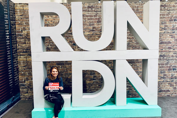 Ruth Bennett, marathon runner, poses in front of a 'RUN LDN' sign after registering for the event